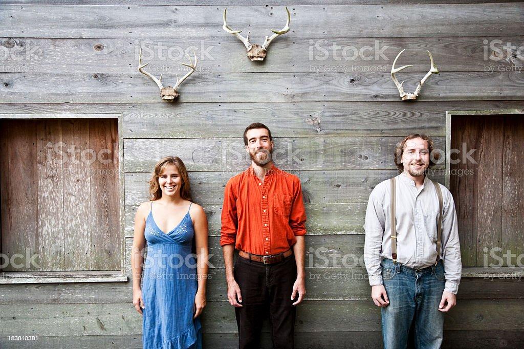 Three people standing under mounted deer antlers royalty-free stock photo