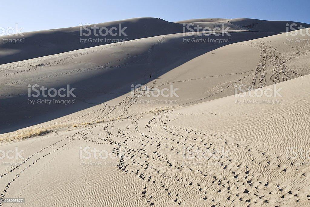 Three people walking through sand dunes leaving footprints stock photo