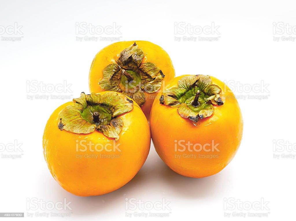 Três persimmons isolado no fundo branco foto royalty-free