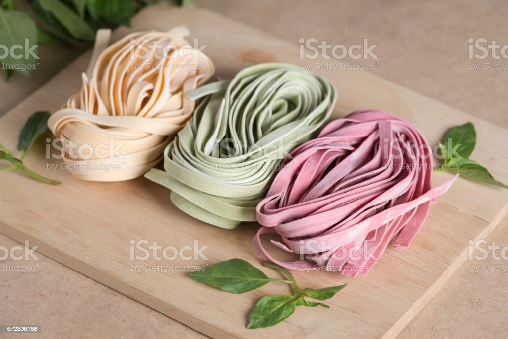 Three pieces of colorful raw italian fettuccine pasta with basil. stock photo