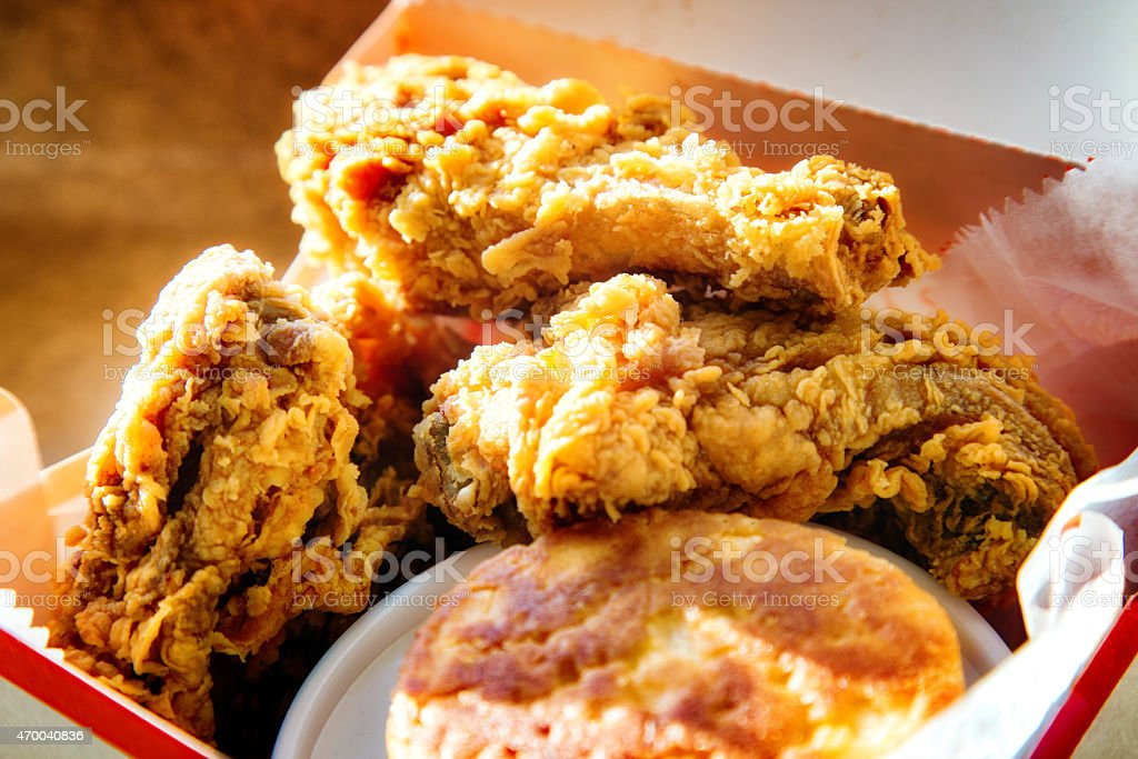 Three pieces of fried chicken in a box with biscuit stock photo