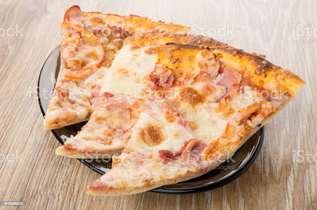 Three pieces of pizza in black oval dish on table stock photo