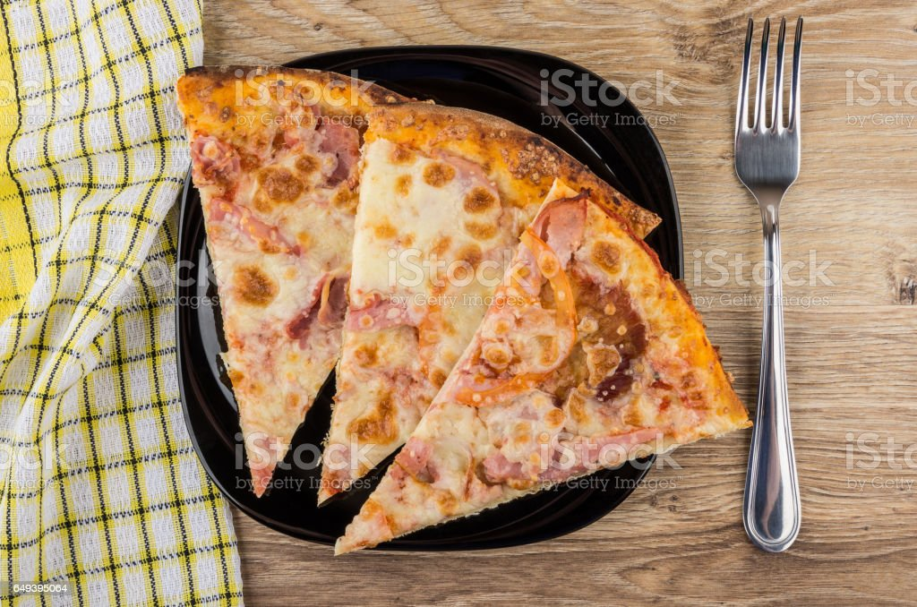 Three pieces of pizza in black plate, napkin and fork stock photo
