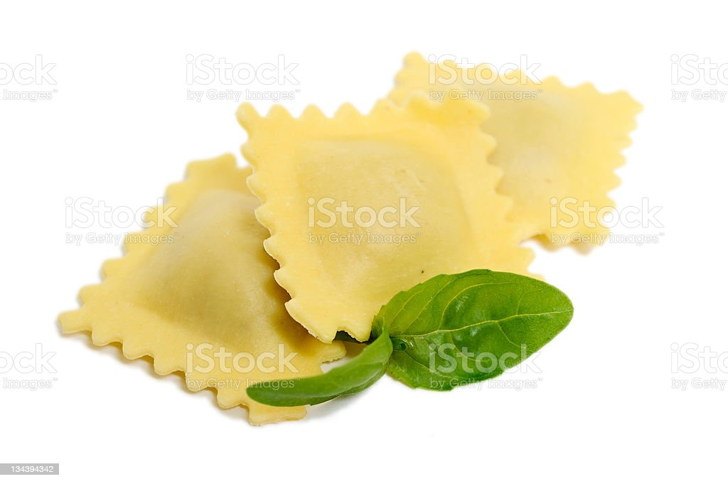 Three pieces of ravioli with two basil leaves stock photo