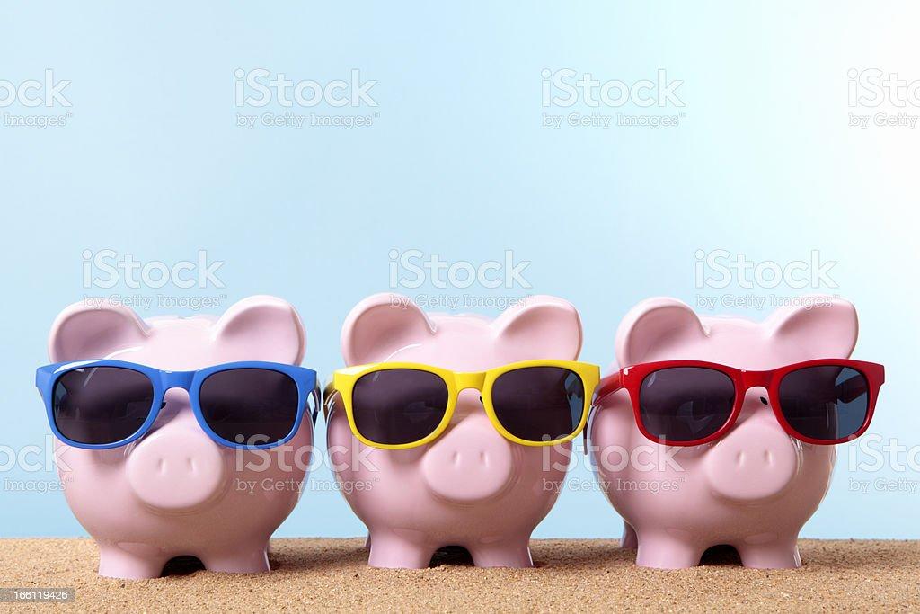 Three piggy banks on beach vacation stock photo