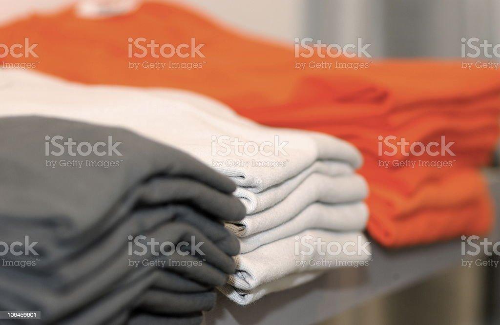 Three piles of shirts in dark gray, white, and bright orange royalty-free stock photo