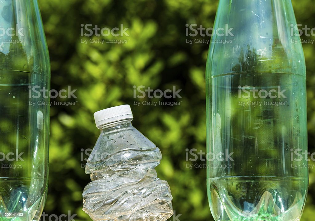 Three plastic bottles with one bottle crushed royalty-free stock photo