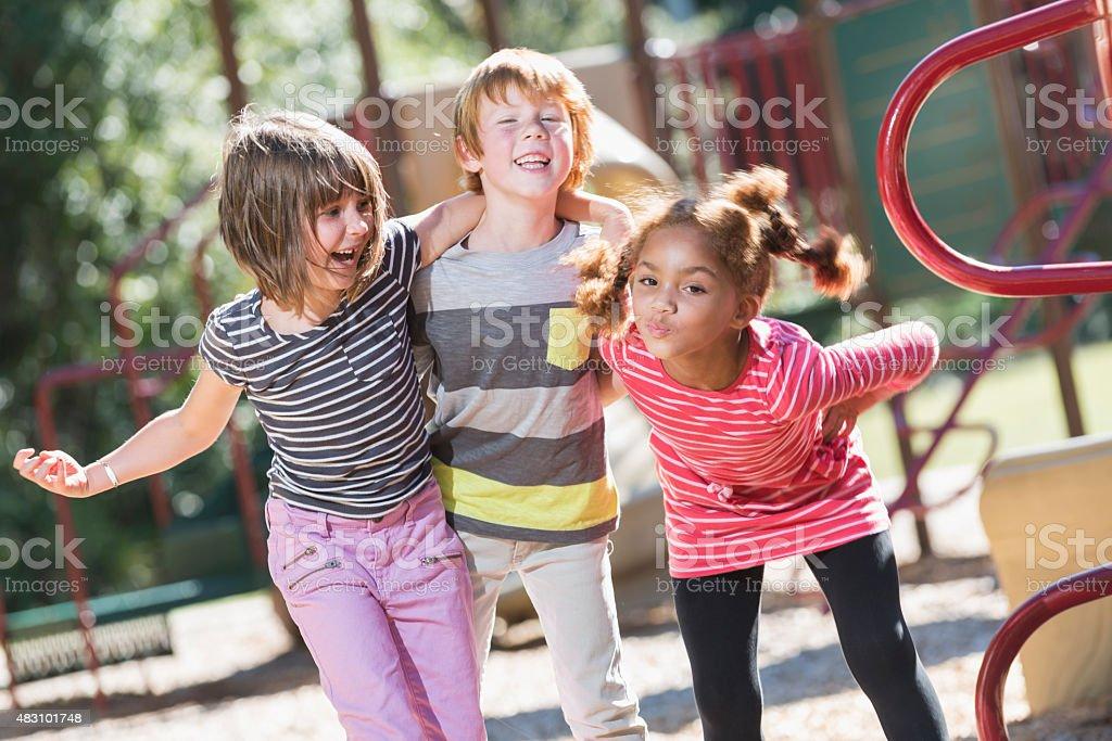 Three playful multiracial children on playground stock photo