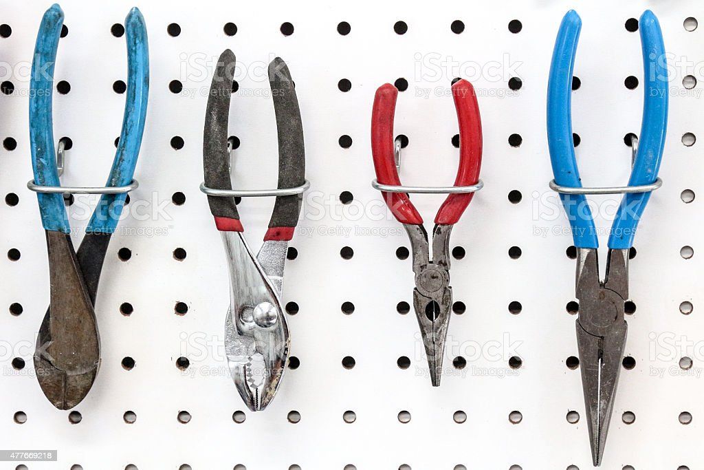 Three pliers and a wire cutter hanging on white pegboard stock photo