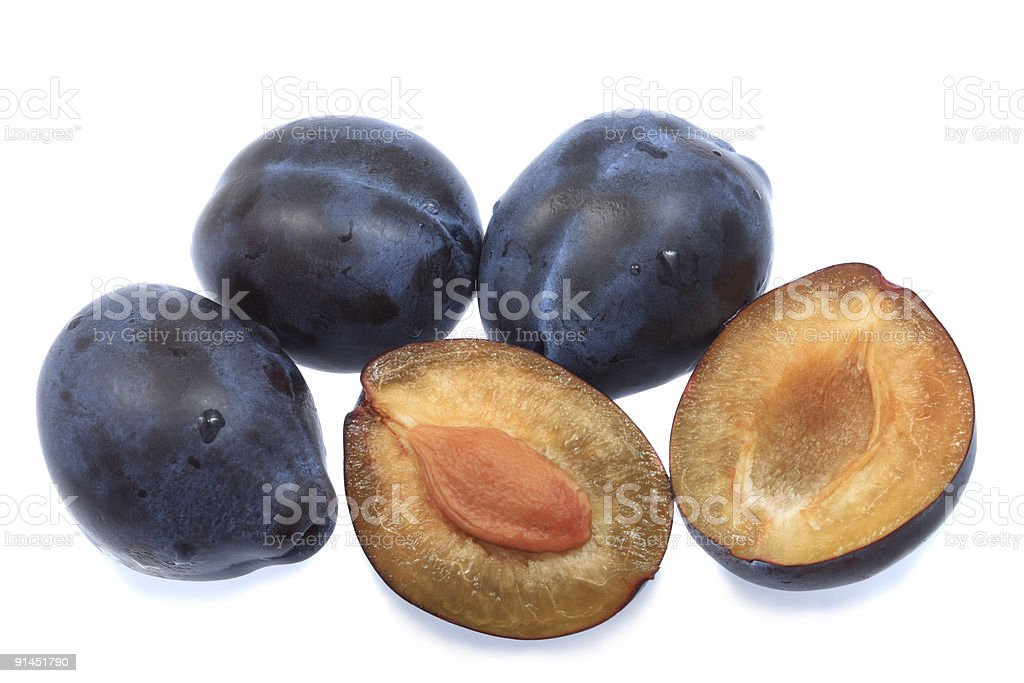 Three plums and one halved royalty-free stock photo