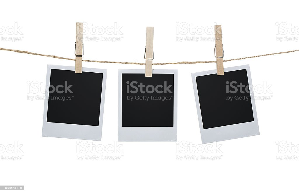 Three Polaroid pictures hanging on a clothesline with pins stock photo