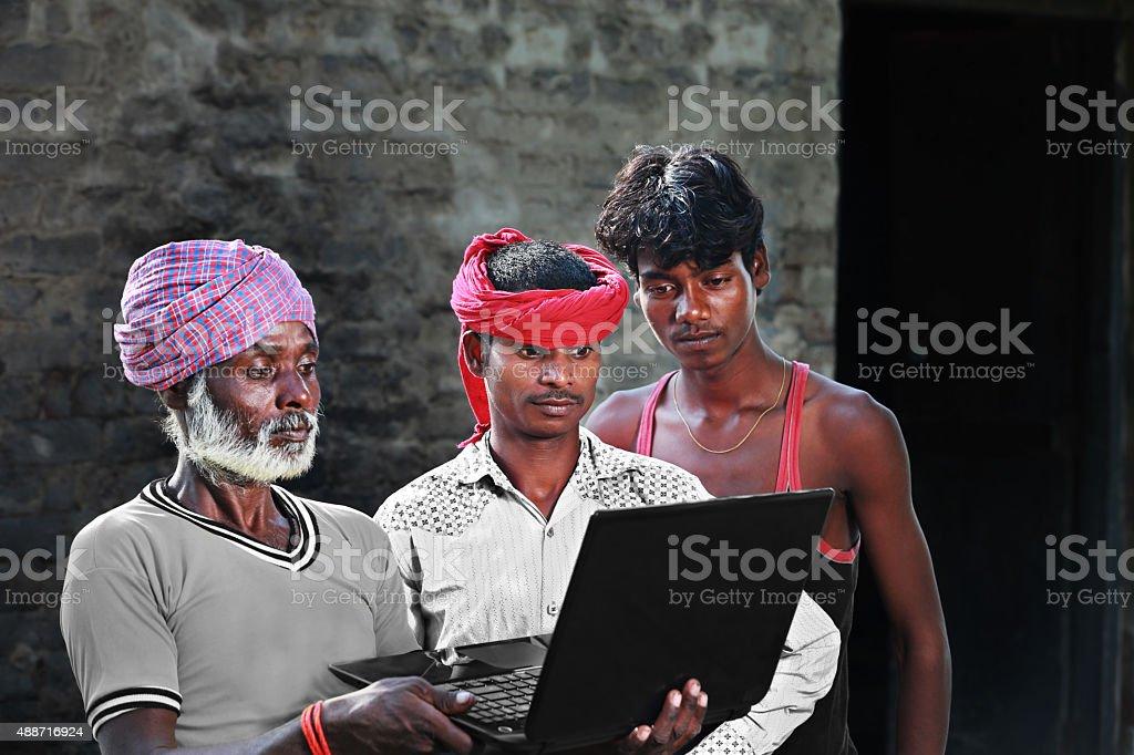Three Poor People Standing Holding Laptop stock photo
