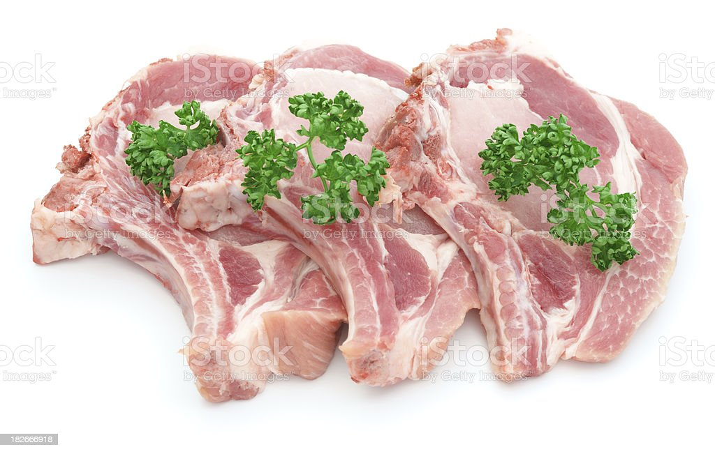 Three pork chops isolated on white decorated with parsley royalty-free stock photo