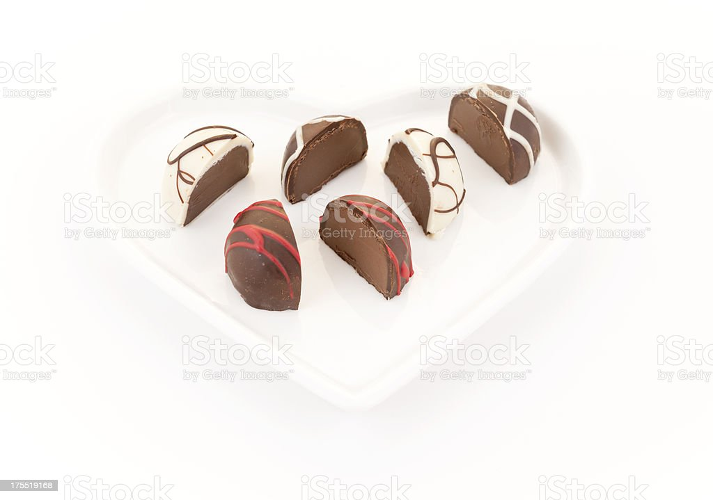 Three Pralines Cut in Halves on Heart Plate royalty-free stock photo