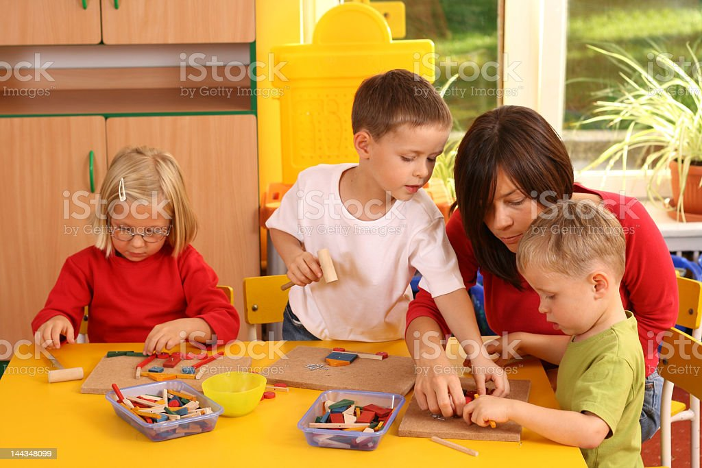 Three preschoolers with teacher at yellow table royalty-free stock photo