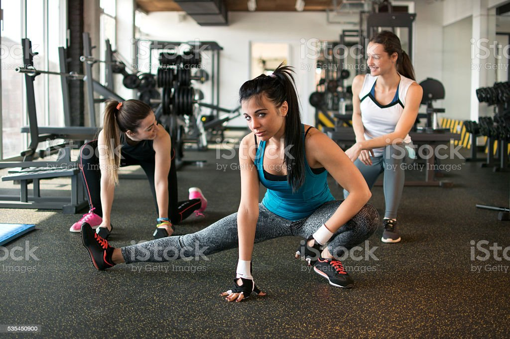 Three pretty girls workout in the gym. stock photo