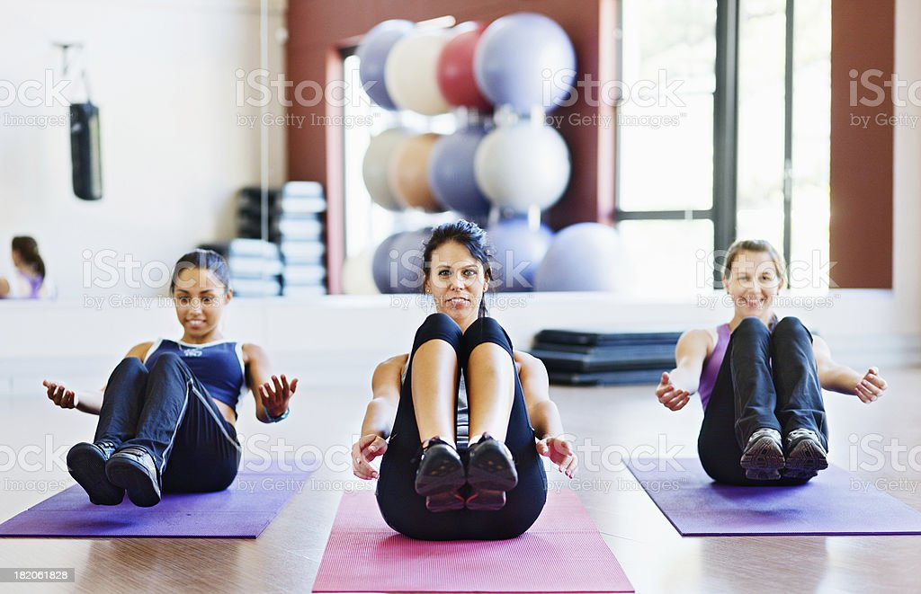 Three pretty women improving core strength with Boat exercise stock photo