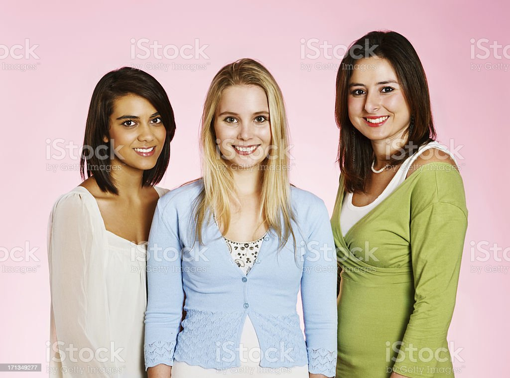 Three pretty young women looking at camera and smiling stock photo