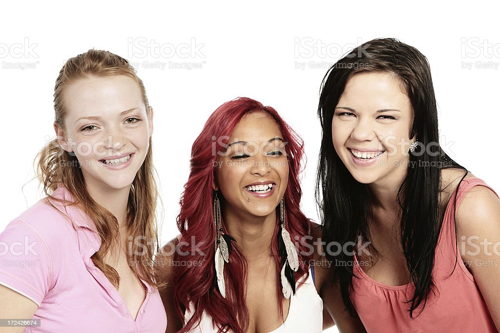 Three pretty young women stand together laughing happily royalty-free stock photo