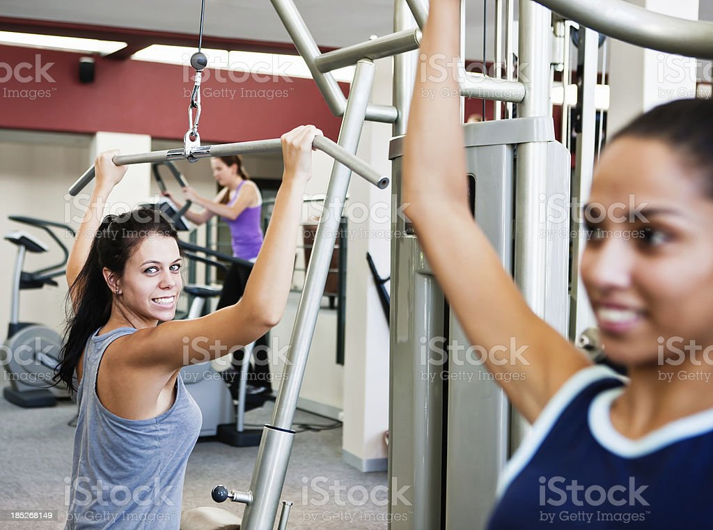 Three pretty young women using exercise equipment to get fit stock photo