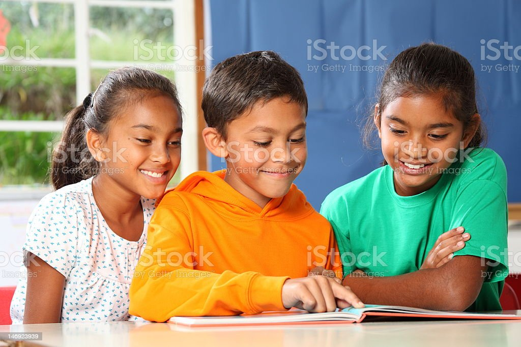 Three primary school children reading and learning together in class royalty-free stock photo