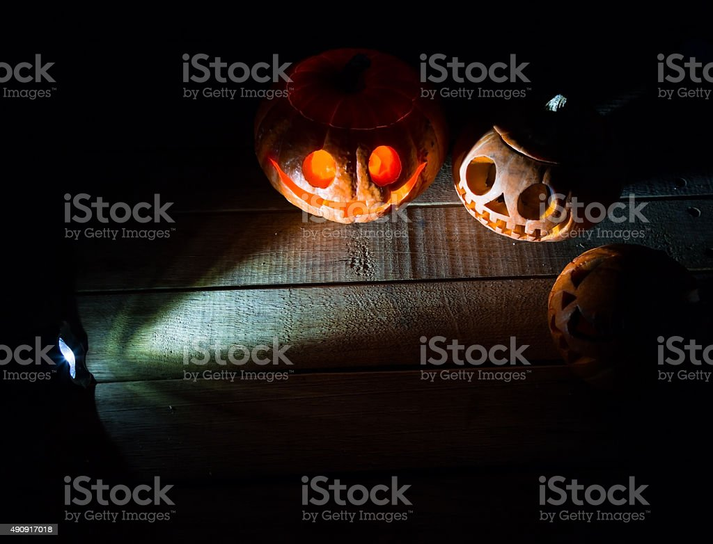 Three pumpkins face on a wooden deck with flashlight. stock photo