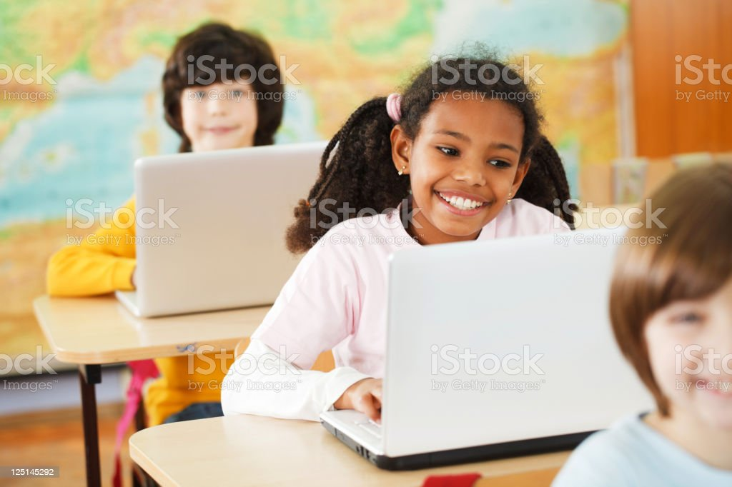 Three pupils sitting in a row and using their laptops royalty-free stock photo