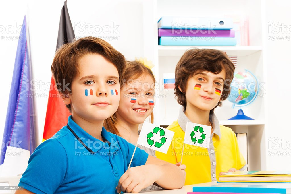 Three pupils sitting in class at ecology lesson stock photo
