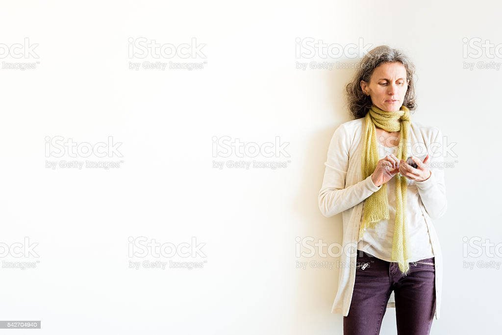 Three quarter length view of mature woman using smart phone stock photo