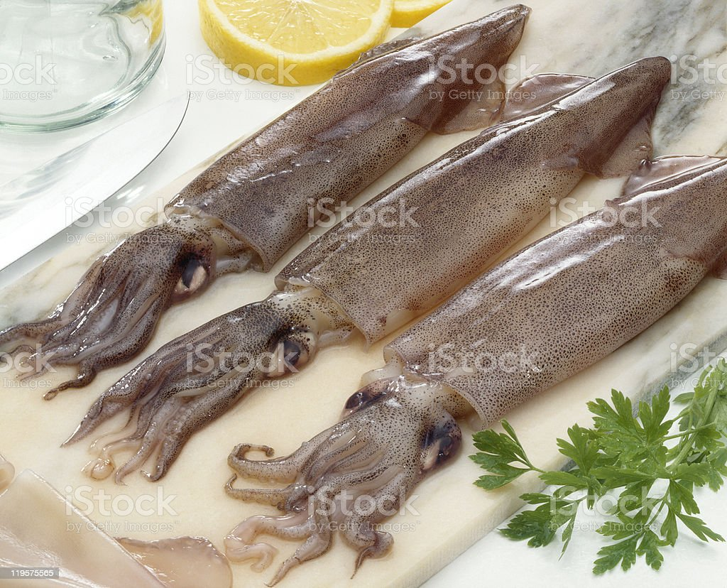 Three raw squids laid out on a chopping board stock photo