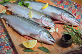 Three raw trout with spices on an old wooden background.