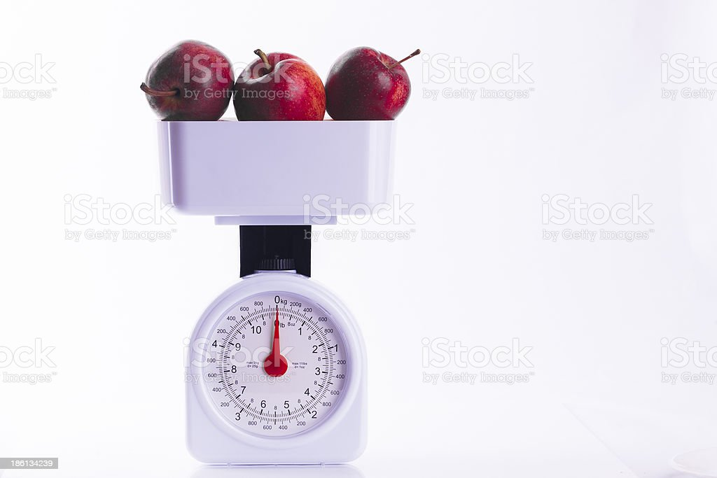 Three red apples on weighing scales royalty-free stock photo
