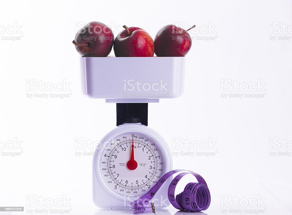 Three red apples on weighing scales with tape measure royalty-free stock photo