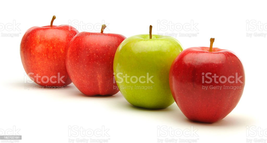 Three red apples with one green against a white background royalty-free stock photo