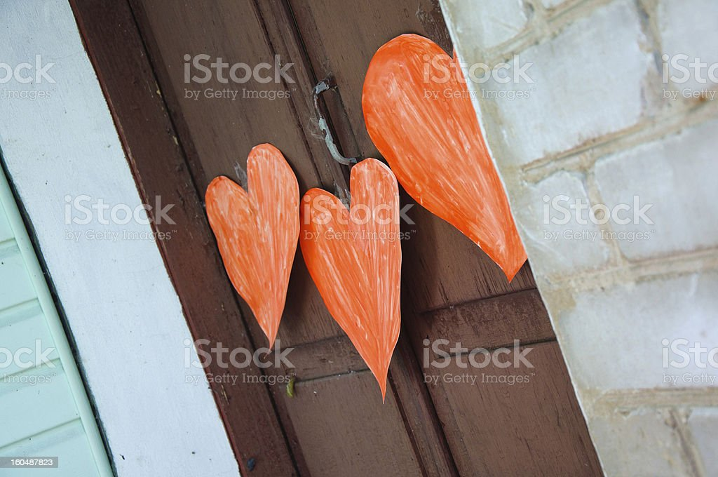 three red cutout heart attach on door. Valentine's Day symbol royalty-free stock photo