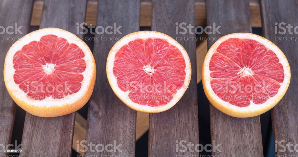 Three red grapefruits on a wooden table stock photo