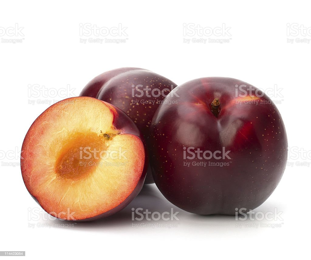 Three red plums - one cut in half and pitted - on white stock photo