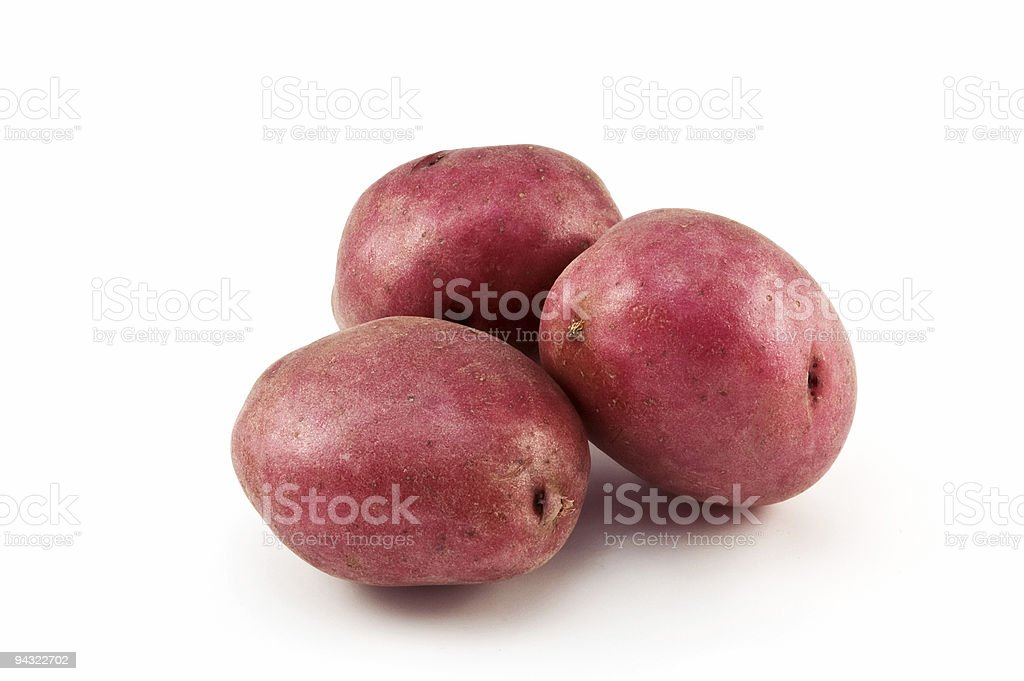 Three red potatoes on a white background stock photo