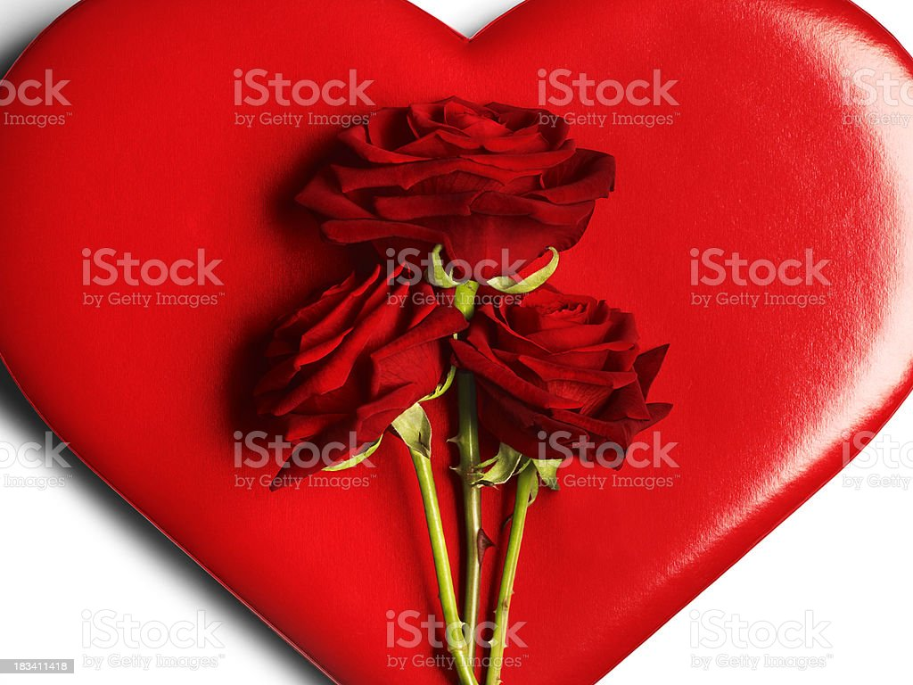 Three red roses on heart background stock photo