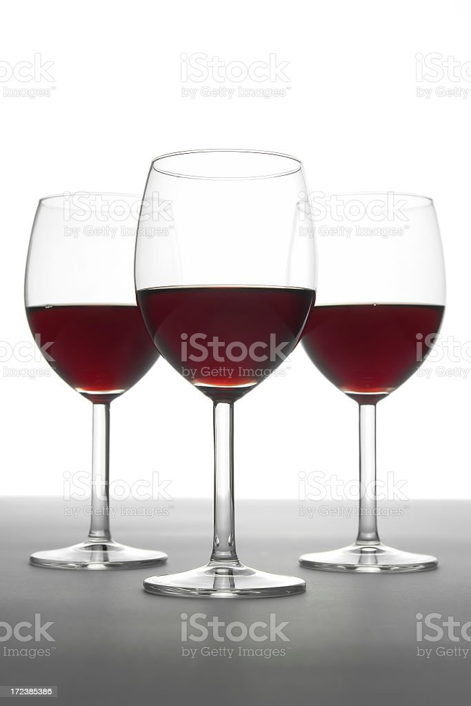 Three red wine glasses standing on gray table, white background royalty-free stock photo