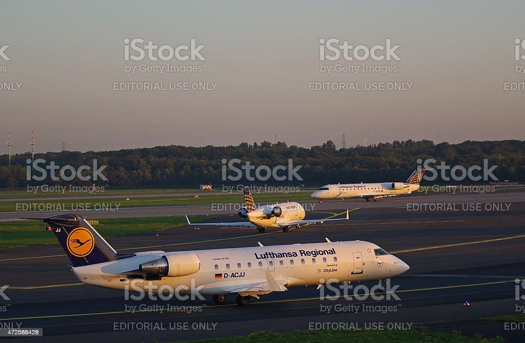 Three regional jets reaching the runway stock photo