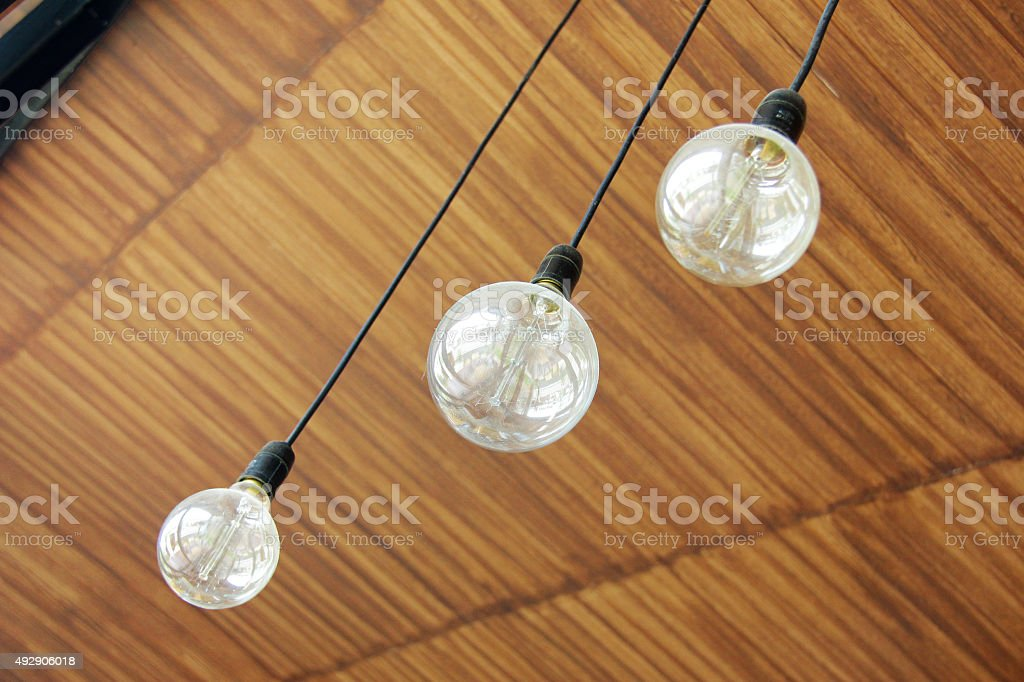 Three retro light bulbs hanging from ceiling stock photo