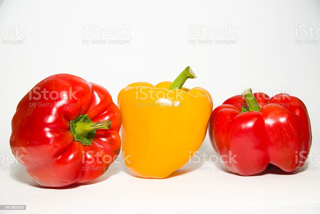 Three ripe red and yellow peppers on over white stock photo