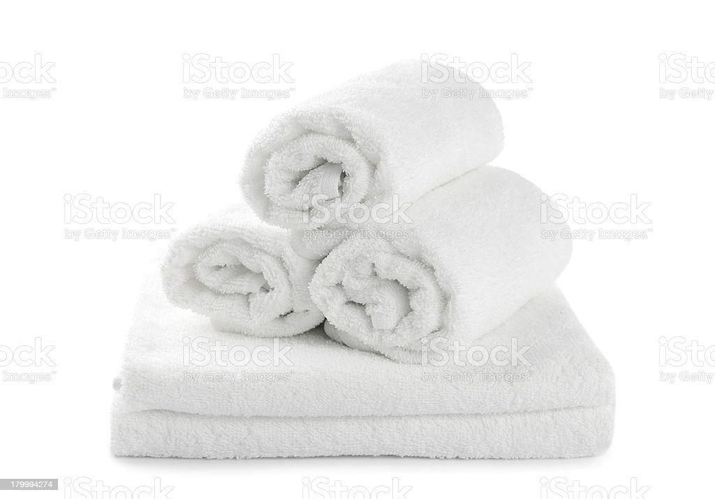 Three rolled up white towels on two folded white towels stock photo