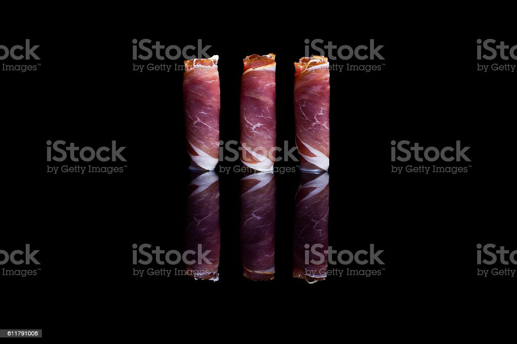 Three rolls of prosciutto ham positioned vertically stock photo