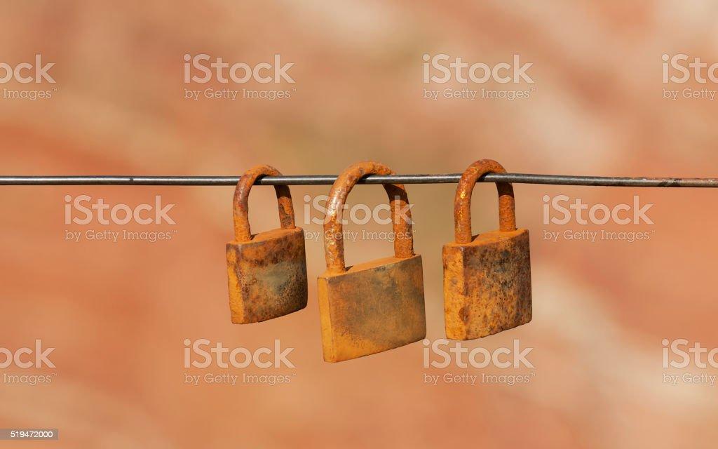 Three rusty padlocks hang on sling. stock photo