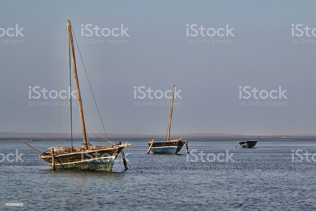 Three sailing dhows in the ocean stock photo