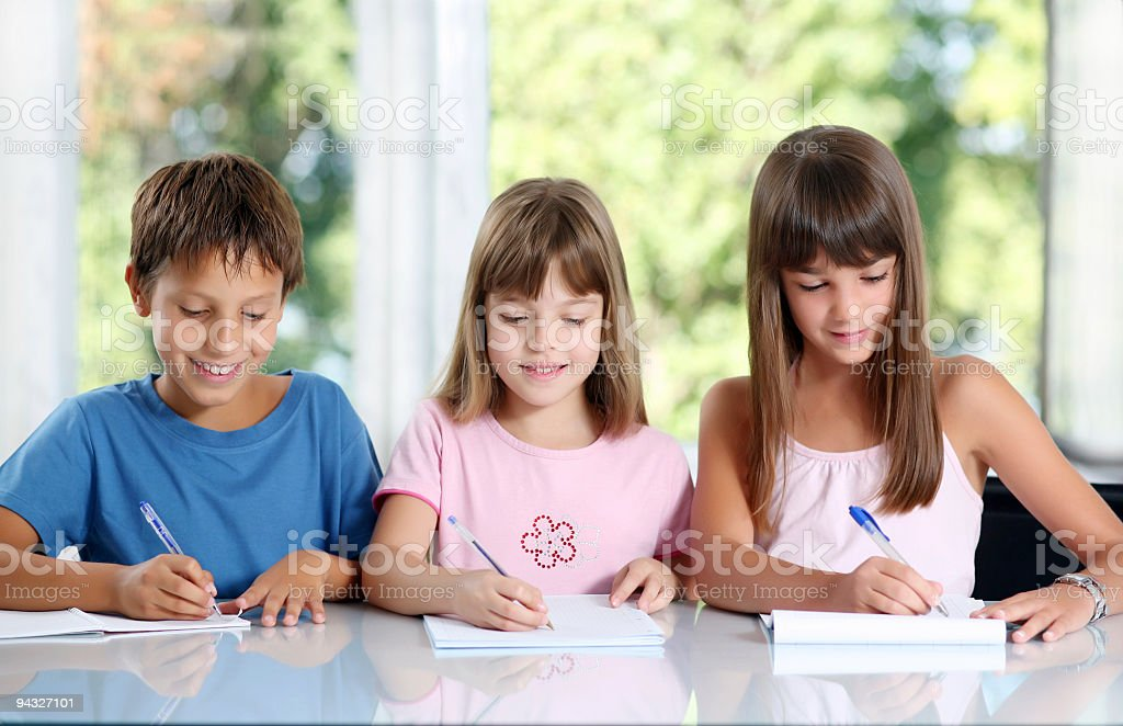 Three schoolchildren writing in classroom. royalty-free stock photo