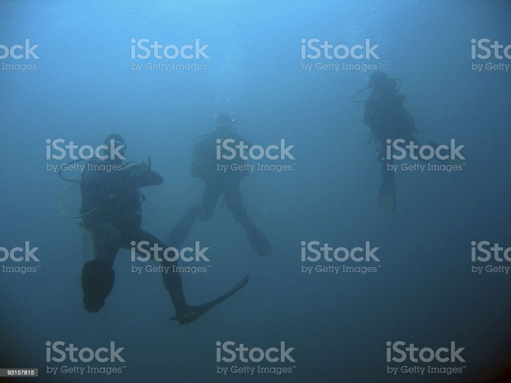 three scuba divers on deep dive royalty-free stock photo