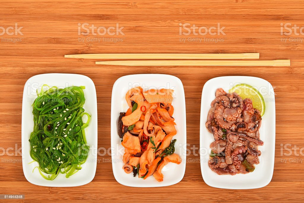 Three seafood salads with chopsticks on wood royalty-free stock photo